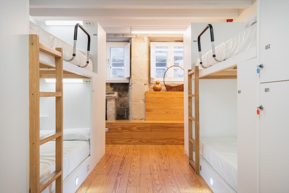 Fotografía interior de una habitación con literas con luces personalizadas, taquillas y dos ventanas.
