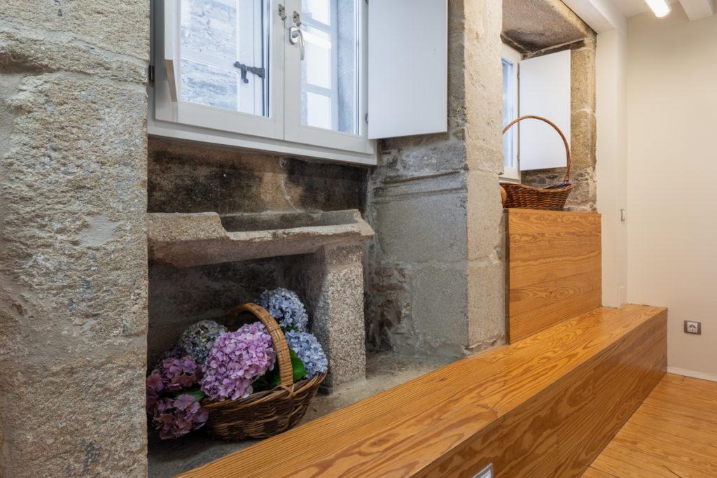 Fotografía de detalle de muro de piedra antiguo con ventanas al exterior y un banco de madera.