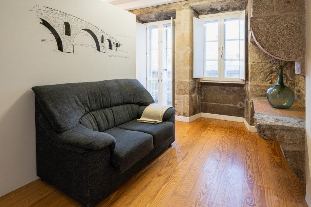 Fotografía del interior de una habitación con sofá de dos plazas, pared con con una ilustración decorativa, una ventana y un balcón.