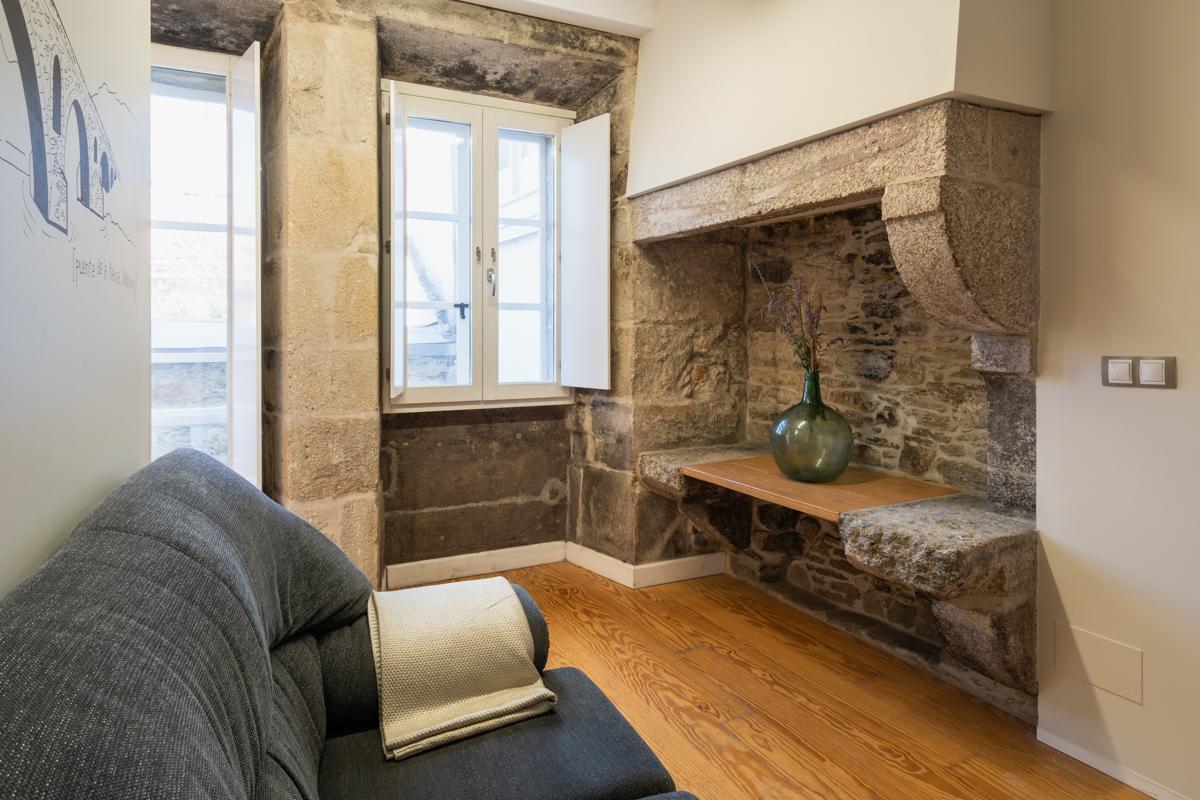 Fotografía del interior de una habitación con sofá de dos plazas, una repisa con un jarón decorativo, una ventana y un balcón.