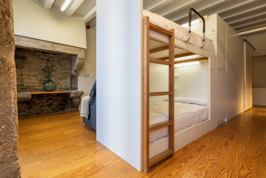 Fotografía del interior de una habitación con literas, luz personalizada en cada cama y taquillas.
