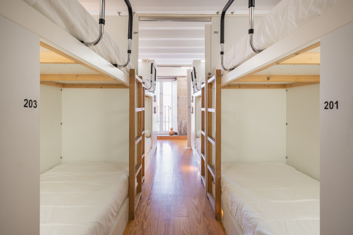 Fotografía del interior de una habitación con literas y taquillas, y al fondo la puerta del balcón.