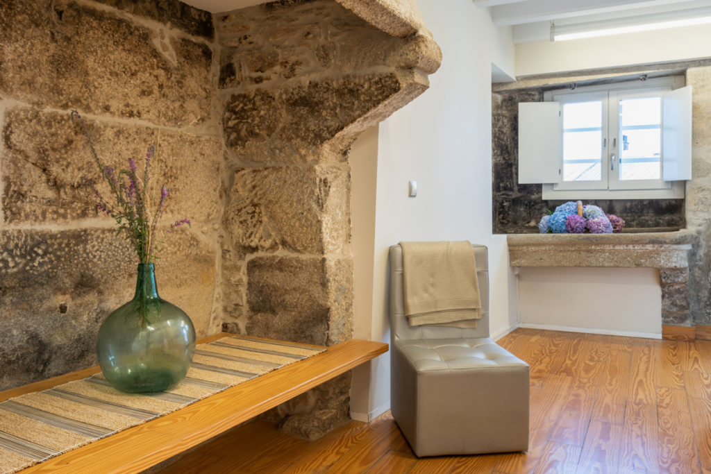 Fotografía del interior de una habitación con muro de piedra y un lavadero antiguo, una silla junto a una repisa con un jarrón decorativo.