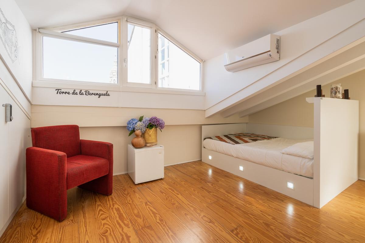 Fotografía del interior de la habitación del ático con cama individual con iluminación personalizada, un sillón, una nevera, aire acondicionado, taquilla con seguro y ventanas..
