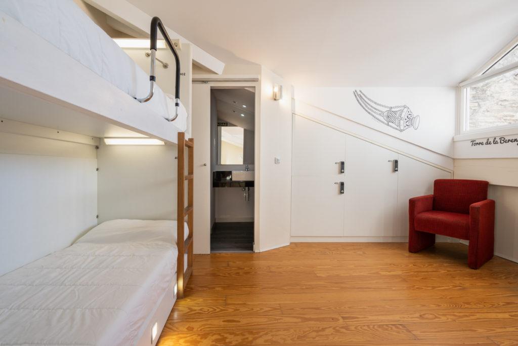 Fotografía del interior de una habitación de ático con una litera con luz personalizada, unas taquillas, un sillón debajo de la ventana y una puerta que da a un baño.