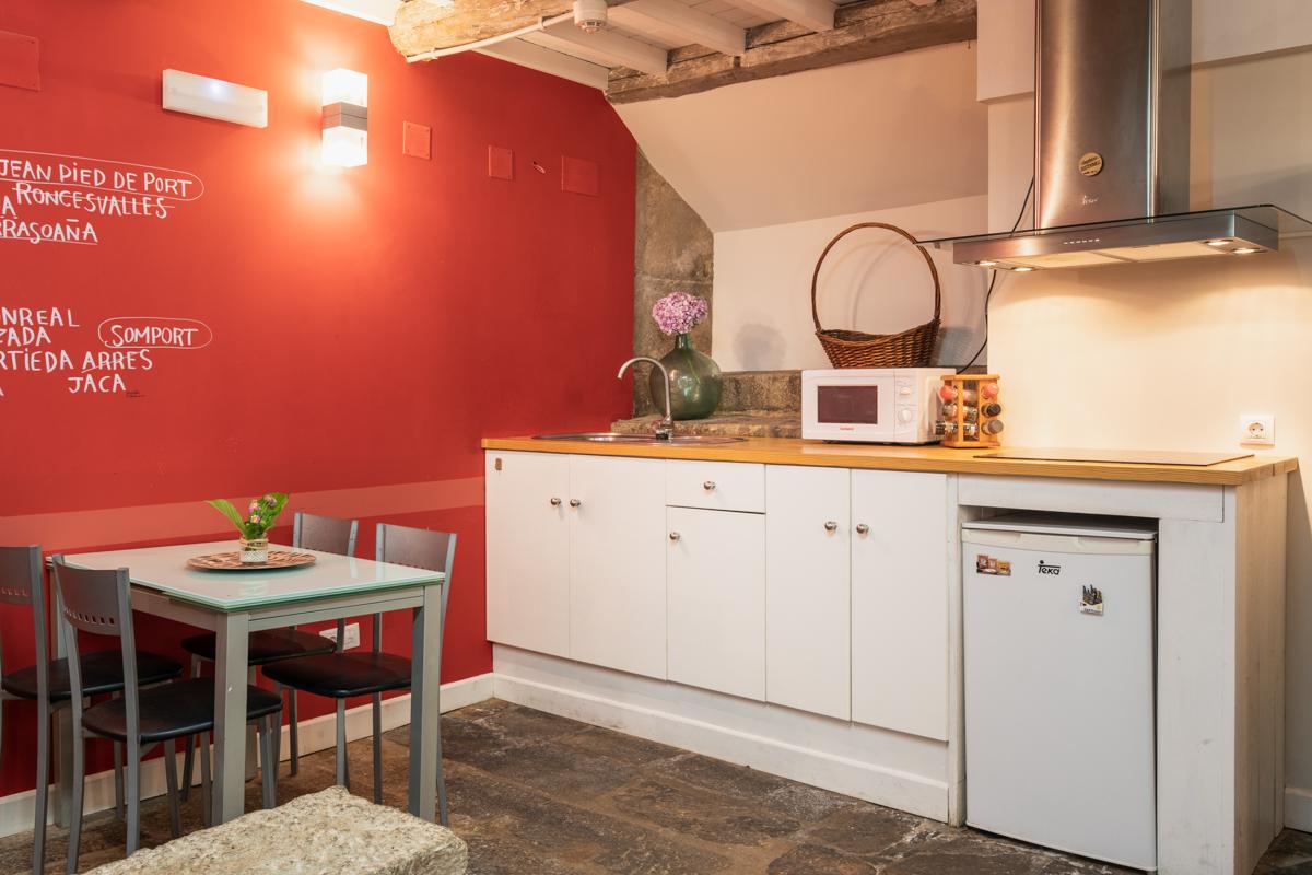 Fotografía de la cocina con fregadero, microondas, nevera pequeña y vitrocerámica con extractor, una mesa con cuatro sillas.