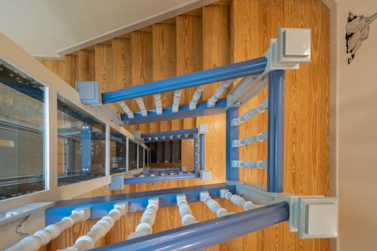 Fotografía del núcleo de escaleras de madera con pasamanos pintado de azul y ascensor acristalado.