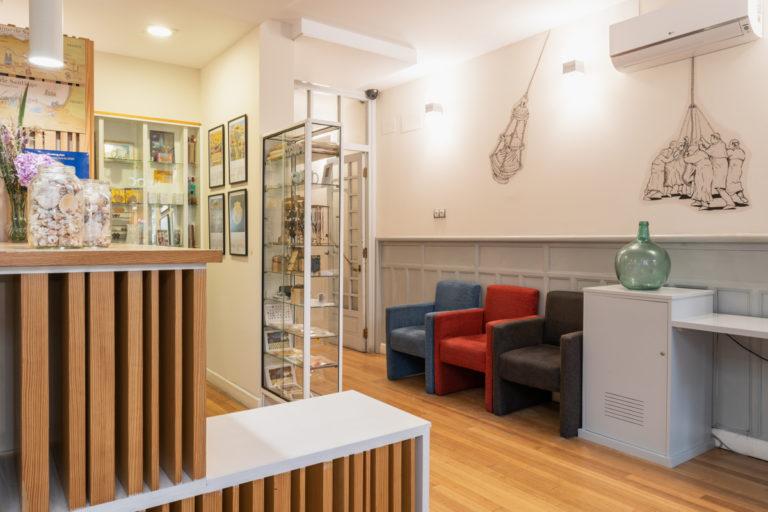 Fotografía de la recepción con zona de descanso, una pequeña sección de souvenirs, aire acondicionado y paredes decoradas con ilustraciones.
