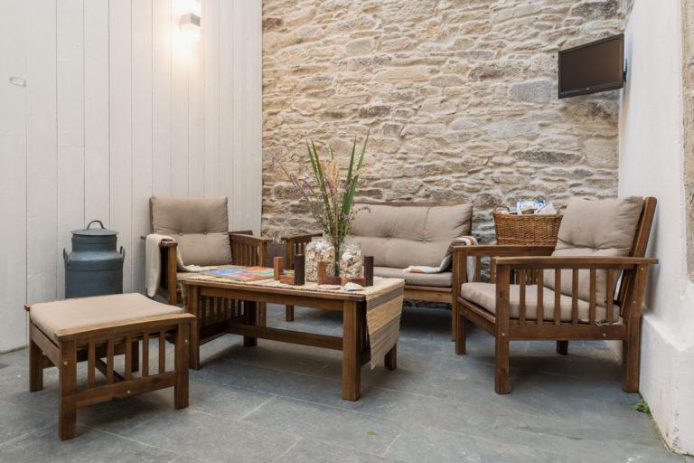 Fotografía de la zona de descanso en patio interior cubierto con unos sillones, una mesa, una televisión, juegos de mesa y revistero.