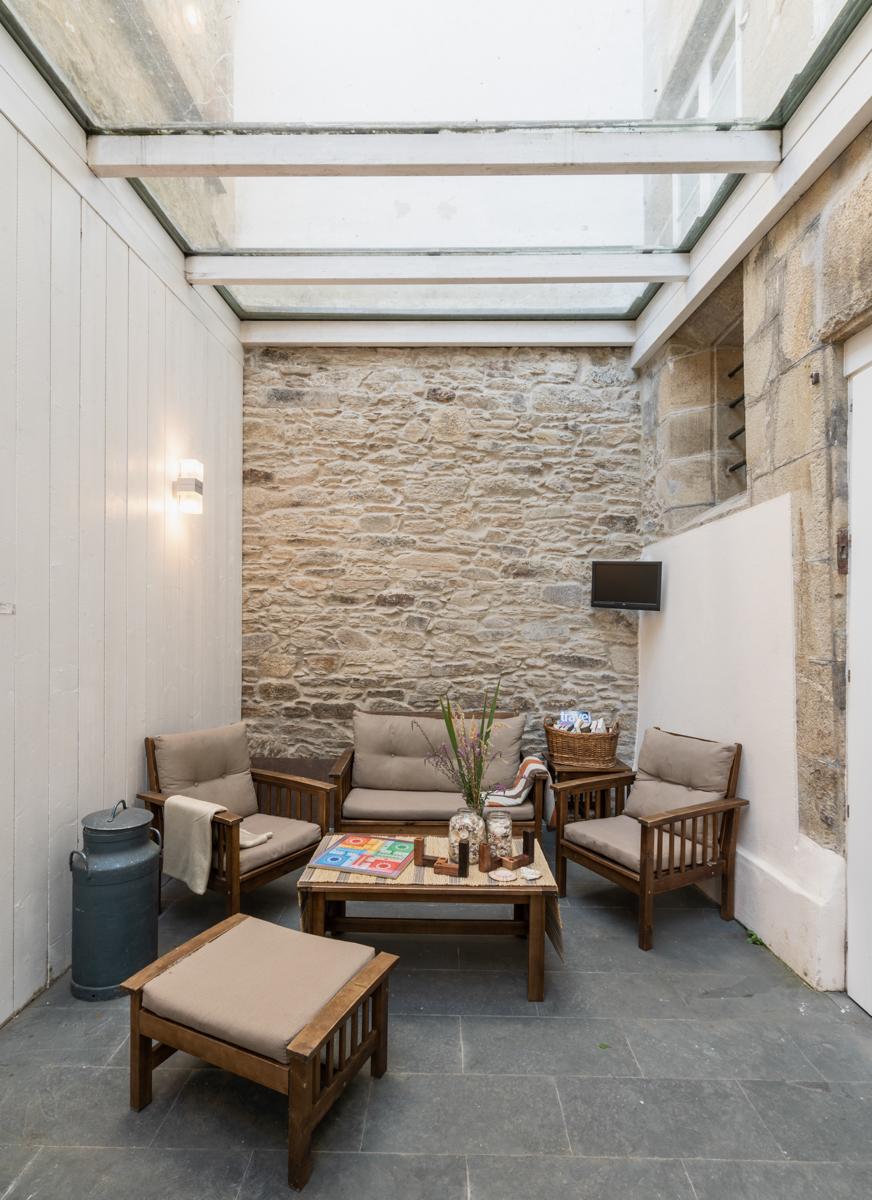 Fotografía de zona de descanso con techo acristalado, sillones y mantas, una mesa con jarrones decorativos y un juego de mesa, y un revistero.
