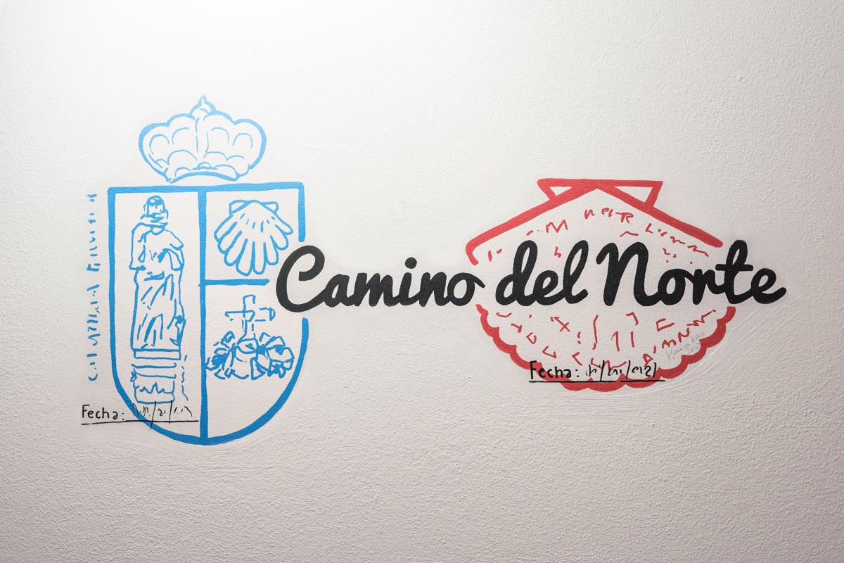 Ilustración en pared de sellos y escrito Camino del Norte.