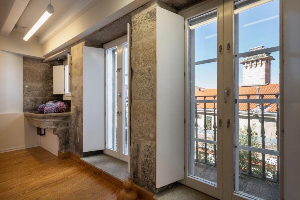 Fotografía del interior de una habitación con muros de piedra y un antiguo lavadero, y dos balcones con vistas a la calle.