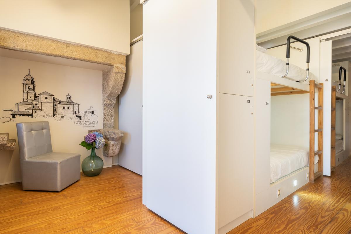 Fotografía del interior de una habitación con literas y taquillas, muros decorados con ilustración, una silla y un jarrón decorativo en el suelo.