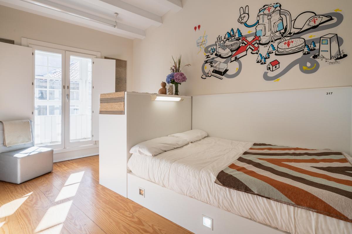 Fotografía del interior de una habitación con cama individual con luz personalizada, pared decorada con ilustración, una silla junto a la puerta del balcón.
