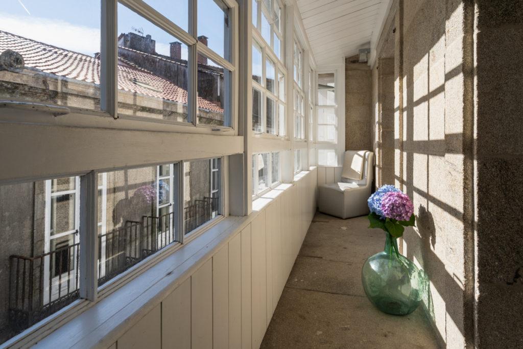 Fotografía de terraza cubierta con vistas a la calle, una silla y un jarrón decorativo en el suelo.