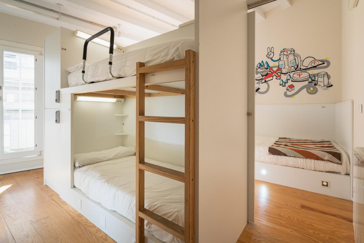 Fotografía del interior de una habitación con literas con luz personalizada, taquillas, paredes decoradas con ilustración y un balcón.