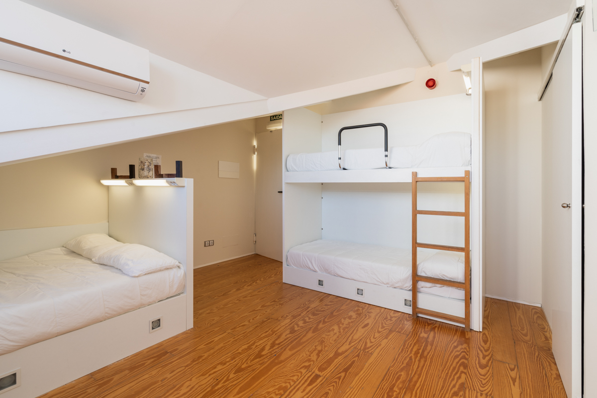 Fotografía del interior de una habitación en un ático con una cama intividual y una litera con luz personalizada, y aire acondicionado.