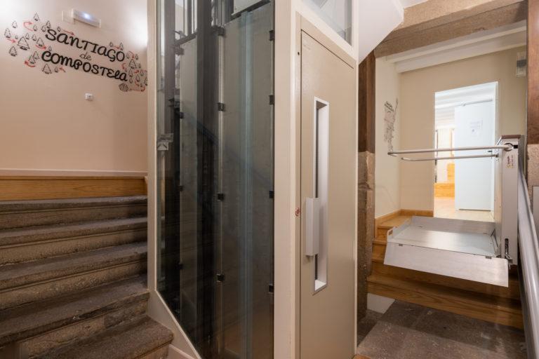 Fotografía de escaleras de piedra, un ascensor y una plataforma salvaescaleras para sillas de ruedas, paredes decoradas con ilustraciones.