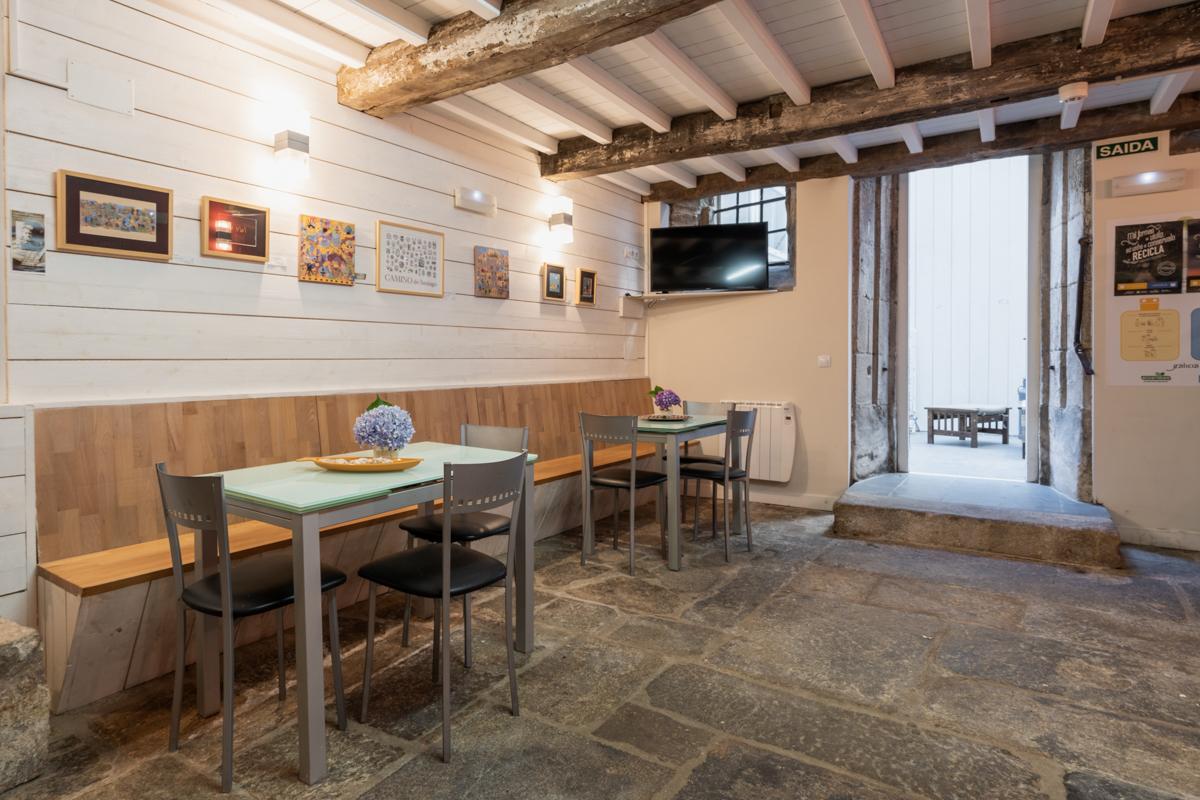 Fotografía del comedor con un banco corrido en la pared, mesas y sillas, una televisión y una puerta que da al patio.