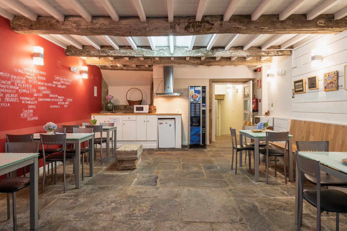 Fotografía de la cocina con fregadero, microondas, nevera pequeña y vitrocerámica con extractor, una maquina de cafés, mesas y sillas, y la puerta de acceso a la cocina.