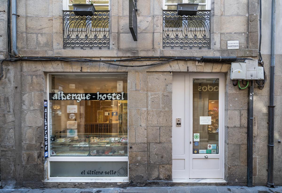 Fotografía del a fachada de piedra del albergue The Last Stamp donde se ve la puerta de acceso y el escaparate con souvenirs.