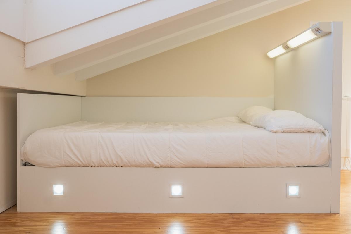 Fotografía de una cama individual con iluminación personalizada en el cabecero y en la base de la cama.