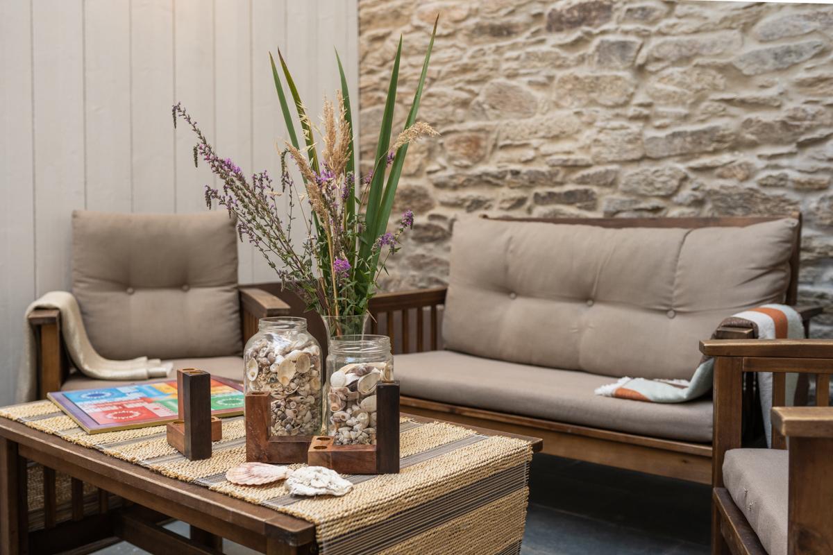 Fotografía de zona de descanso con sillones y mantas, una mesa con jarrones decorativos y un juego de mesa.