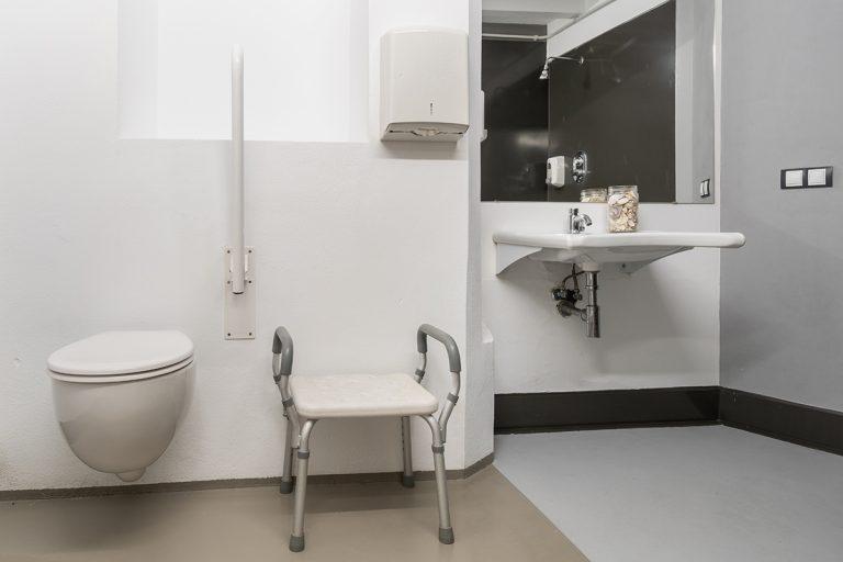 Fotografía de baño adaptado para personas que usen silla de ruedas, con váter, silla, lavabo, espejo, y reflejado en el espejo se aprecia la ducha.